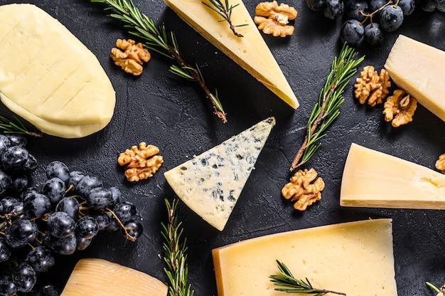 Piękne tło z różnych rodzajów pysznego sera, orzechów włoskich i winogron.