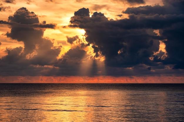 Piękne tropikalne morze ze światłem słonecznym przez dramatyczną chmurę o zachodzie słońca