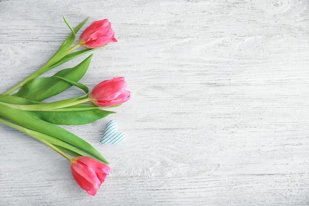 Piękne tulipany i małe bawełniane serduszko na jasnym drewnie