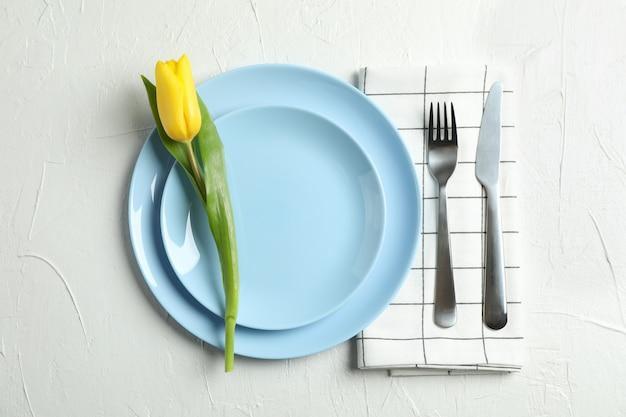 Piękne tulipany i talerz z naczyniami na dzień matki na świetle, widok z góry