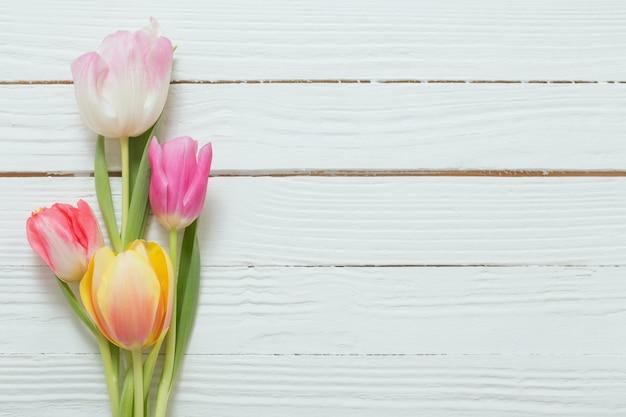 Piękne tulipany na białym drewnianym tle widok z góry