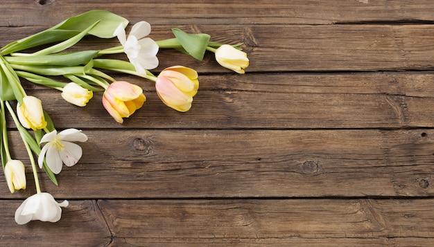 Piękne tulipany na starej ciemnej powierzchni drewnianej