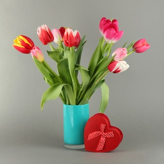 Piękne tulipany w wiaderku z prezentami na szarej przestrzeni