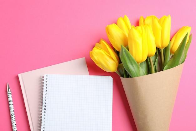 Piękne tulipany z notatnikami na dzień matki na świetle, widok z góry. miejsce na tekst