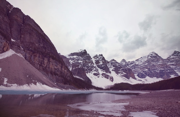 Piękne turkusowe wody jeziora moraine z pokrytymi śniegiem szczytami nad nim w parku narodowym banff w kanadzie