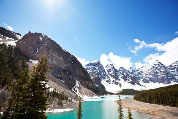 Piękne turkusowe wody jeziora morenowego z ośnieżonymi szczytami nad nim w parku narodowym banff w kanadzie