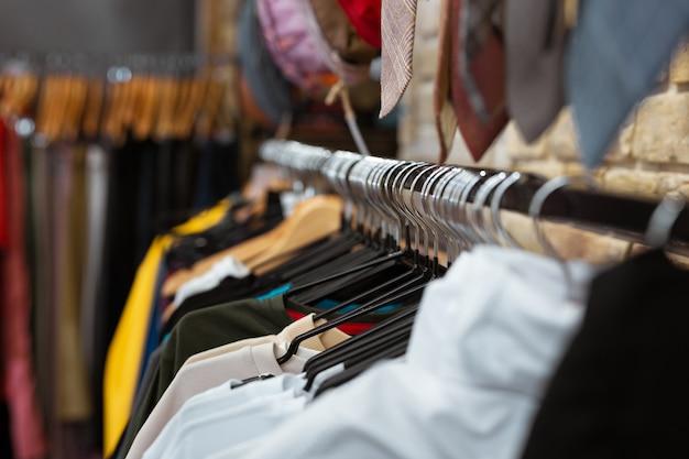 Piękne ubrania. zbliżenie na piękne kolorowe koszulki dla mężczyzn wiszące i dobrze wyglądające w modnym sklepie