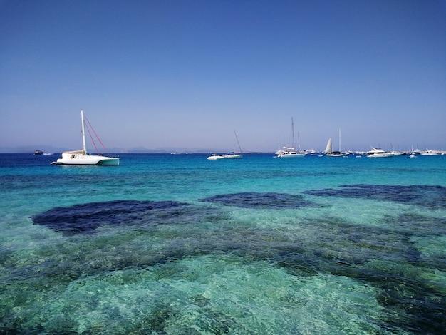 Piękne ujęcie białych łodzi na wybrzeżu w pobliżu formentery w hiszpanii