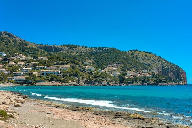 Piękne ujęcie błękitnego oceanu z falami rozpryskującymi się na plaży