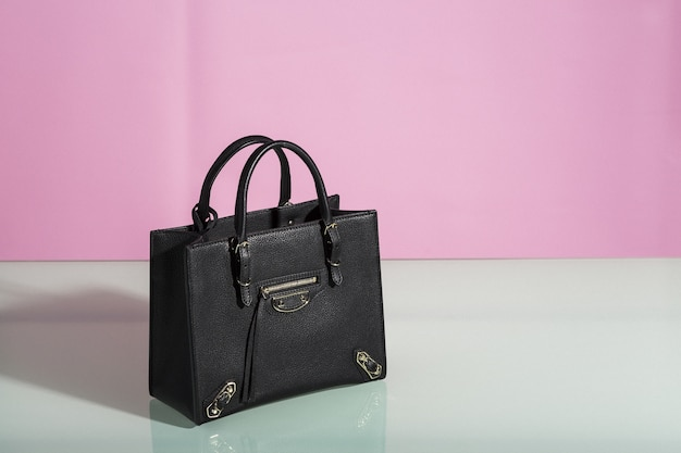 Piękne ujęcie czarnej torebki na białym stole z różem