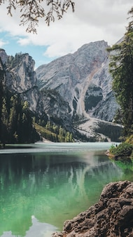 Piękne ujęcie czystego jeziora otoczonego wzgórzami i górami pokrytymi zielenią
