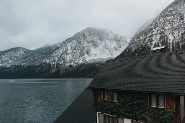 Piękne ujęcie domu w pobliżu jeziora i szarych gór pokrytych śniegiem w ciągu dnia