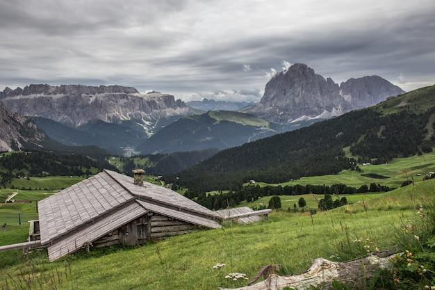 Piękne ujęcie drewnianego domu w zielonej dolinie puez-geisler nature park w miscì we włoszech