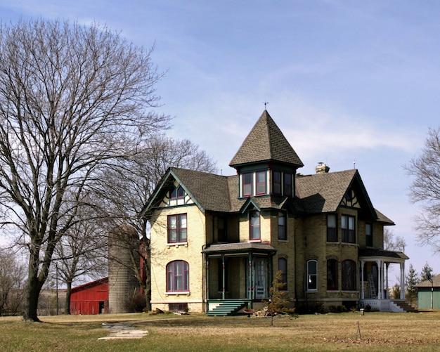 Piękne ujęcie dużego wiejskiego domu w czyste, błękitne niebo
