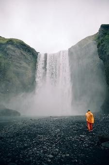 Piękne ujęcie dużego wodospadu z pojedynczym mężczyzną w jasnym materiale stojącym na dole