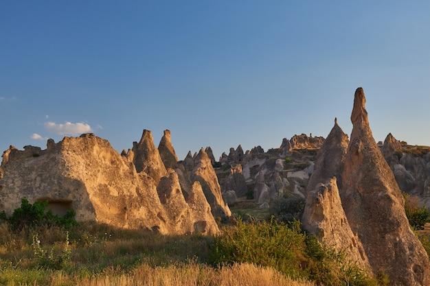 Piękne ujęcie dużych skał na trawiastym wzgórzu pod jasnym, błękitnym niebem