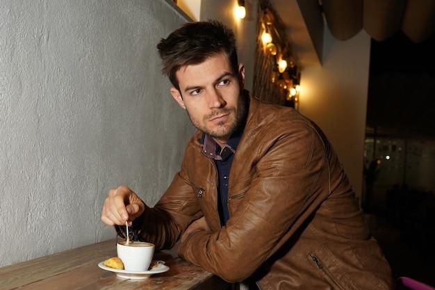 Piękne ujęcie eleganckiego mężczyzny w brązowej skórzanej kurtce mieszającego kawę na drewnianym stole