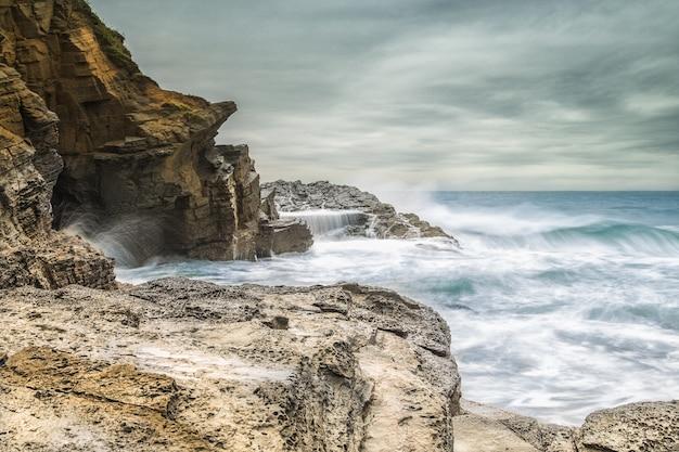Piękne ujęcie fal morskich uderzających o skały na brzegu morza przy zachmurzonym szarym niebie