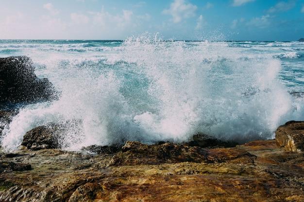 Piękne ujęcie fal morskich uderzających w duże skały w pobliżu brzegu