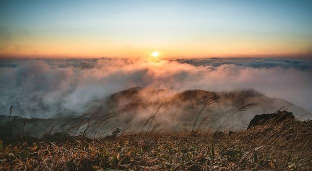 Piękne ujęcie gór pod zachmurzonym niebem o zachodzie słońca