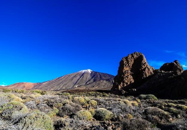 Piękne ujęcie góry, dużych skał i zielonych roślin na bezchmurnym niebie