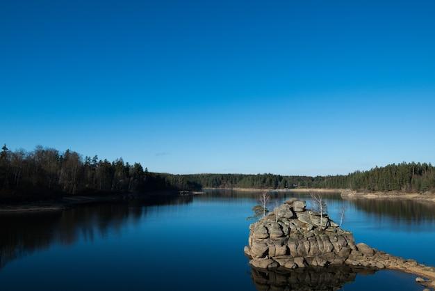 Piękne ujęcie jeziora w lesie, w którym odbija się bezchmurne niebo