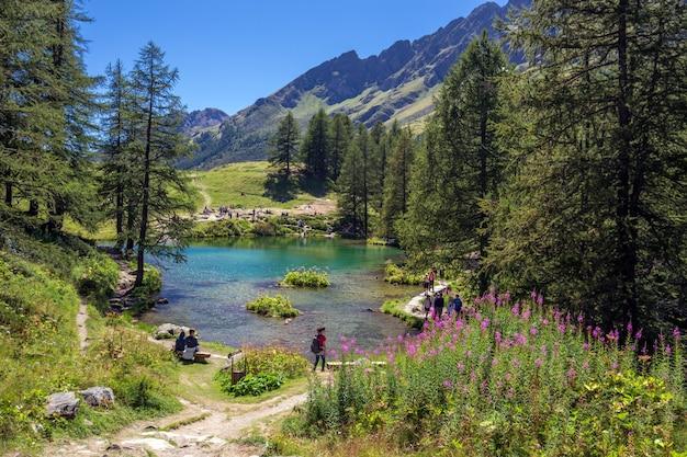 Piękne ujęcie jeziora w pobliżu gór i otoczone drzewami i ludźmi