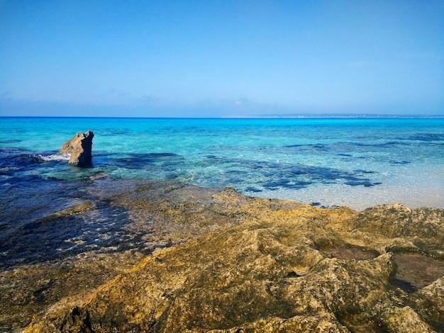 Piękne ujęcie kamienistej plaży na formenterze w hiszpanii