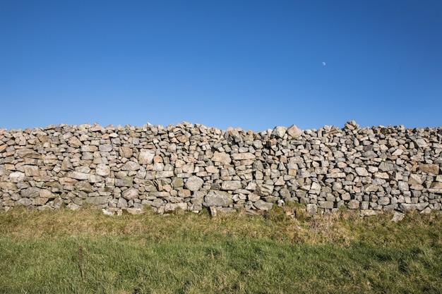 Piękne ujęcie kamiennego muru w zielonym polu pod bezchmurnym niebem