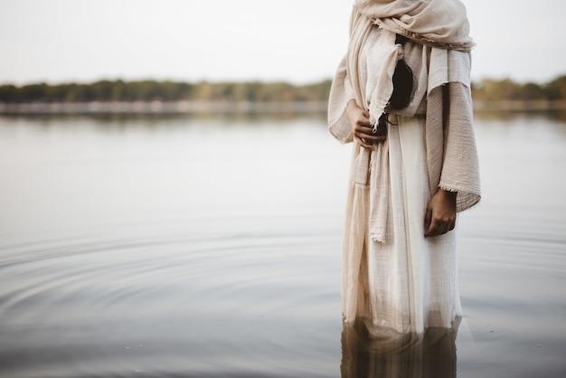 Piękne ujęcie kobiety w biblijnej szacie stojącej w wodzie