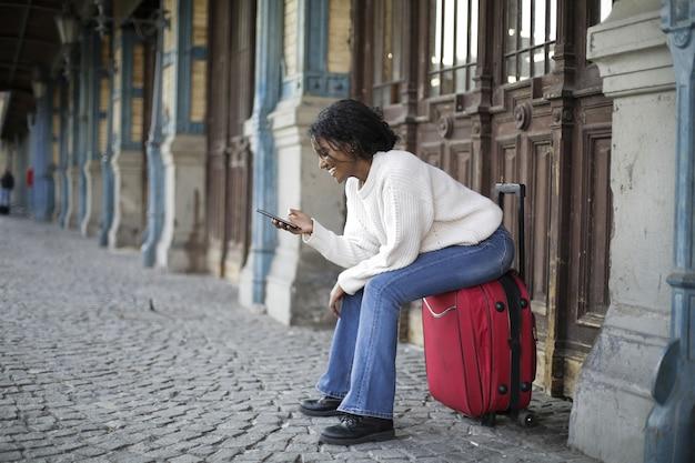 Piękne ujęcie kobiety z białym długim rękawem siedzącej na czerwonym bagażu