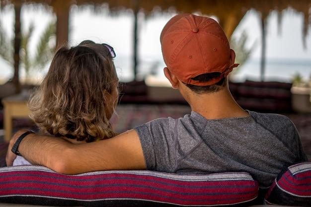 Piękne ujęcie kochającej się pary na wakacjach, siedząc na kanapie i patrząc na morze