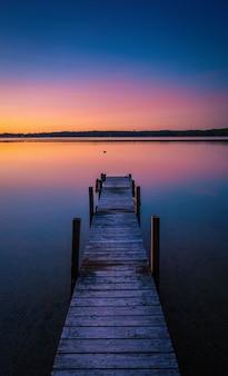 Piękne ujęcie kolorów zachodu słońca na horyzoncie spokojnego jeziora z dokiem