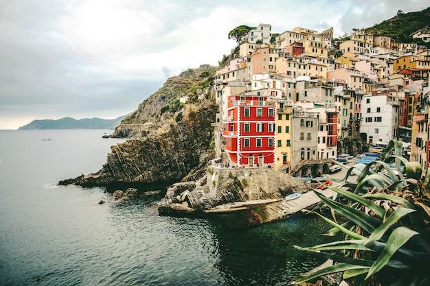 Piękne ujęcie kolorowych budynków na wzgórzu w pobliżu morza w manaroli we włoszech