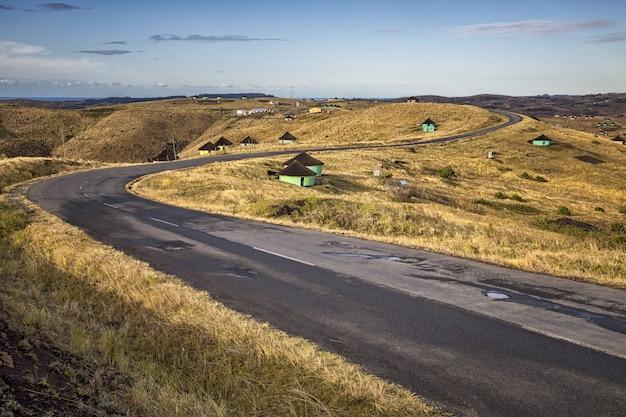 Piękne ujęcie krętej drogi z małymi domkami po bokach i błękitnym niebem