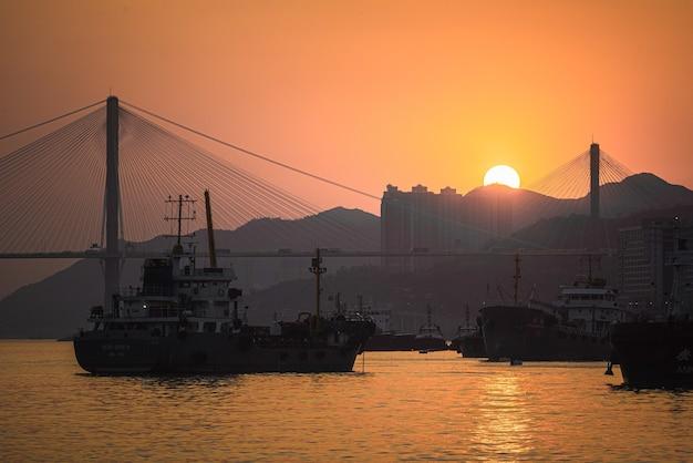 Piękne ujęcie łodzi płynących po morzu z mostem na tle o zachodzie słońca
