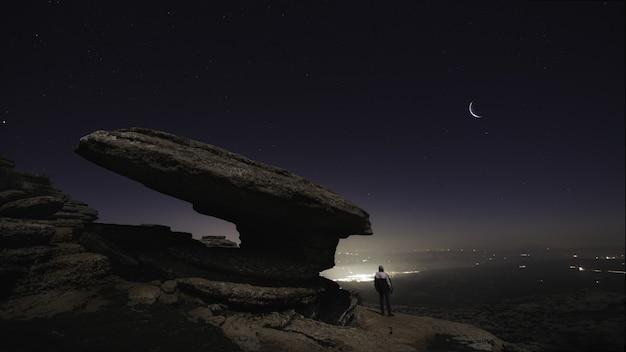 Piękne ujęcie mężczyzny stojącego na wzgórzach pod nocnym niebem