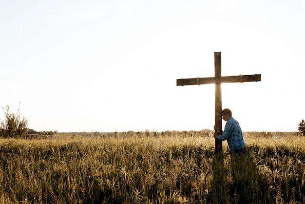 Piękne ujęcie mężczyzny z głową przed drewnianym krzyżem w trawiastym polu