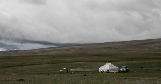 Piękne ujęcie namiotu na trawiastym polu z grubą warstwą chmur na niebie w chłodny dzień