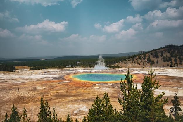 Piękne ujęcie oazy otoczonej lądem i zalesionymi górami