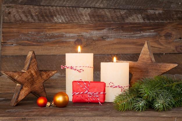 Piękne ujęcie ozdób choinkowych i świec palących się na tle drewnianych