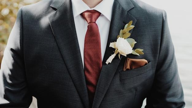 Piękne ujęcie pana młodego z białym kwiatem na garniturze