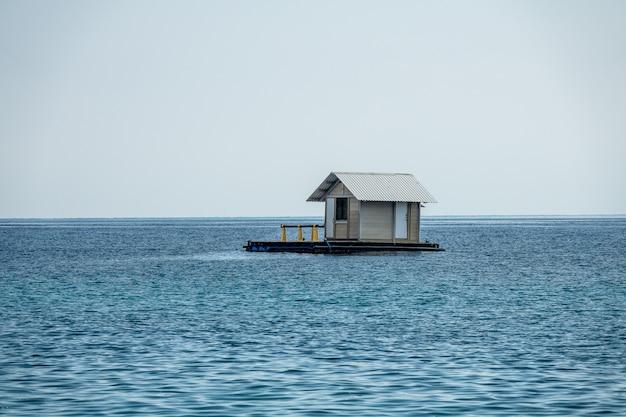 Piękne ujęcie pływającego domu w błękitnym oceanie z czystym, białym niebem w