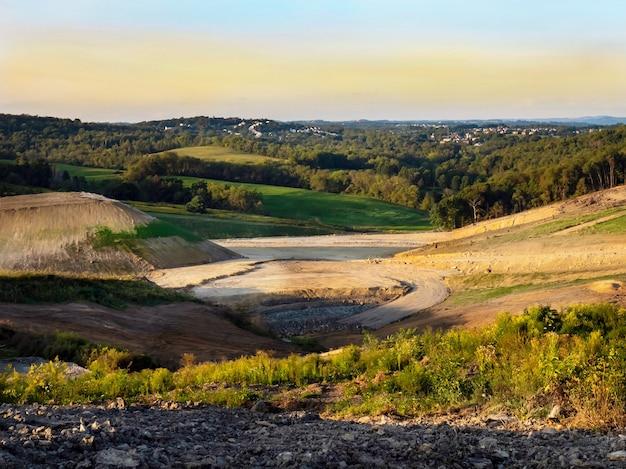 Piękne ujęcie pola otoczonego zalesionymi wzgórzami pod czystym niebem