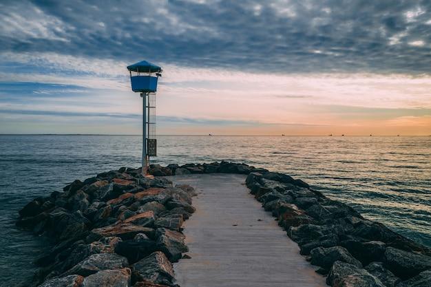 Piękne ujęcie przystani otoczonej kamieniami prowadzącymi do morza o zachodzie słońca