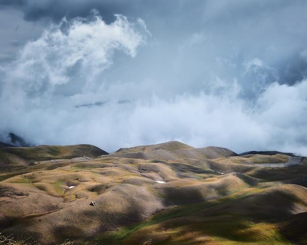 Piękne ujęcie pustych trawiastych wzgórz pod niebieskim pochmurnym niebem