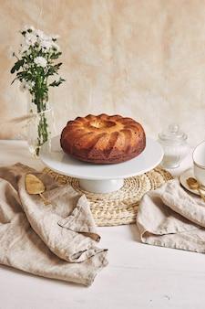 Piękne ujęcie pysznego ciasta pierścieniowego ułożonego na białym talerzu i białego kwiatu w jego pobliżu