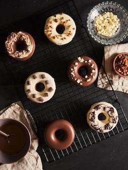 Piękne ujęcie pysznych pączków oblanych polewą czekoladową ze składnikami na stole