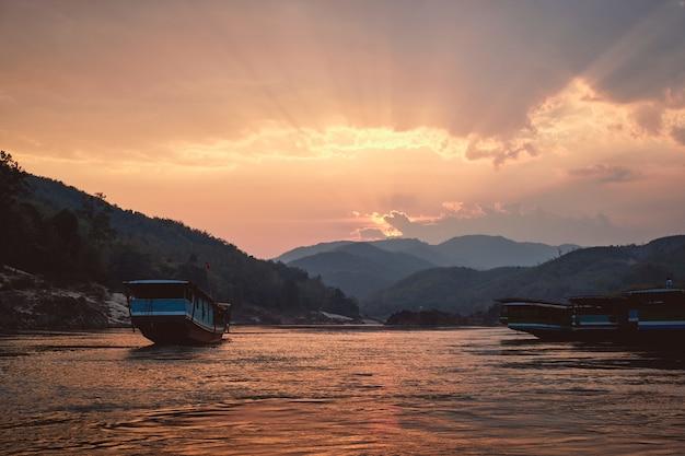 Piękne ujęcie rzeki mekong z łodziami na pierwszym planie o zachodzie słońca w pak beng w laosie
