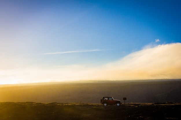 Piękne ujęcie samochodu terenowego na wzgórzu z błękitnym niebem w tle w ciągu dnia